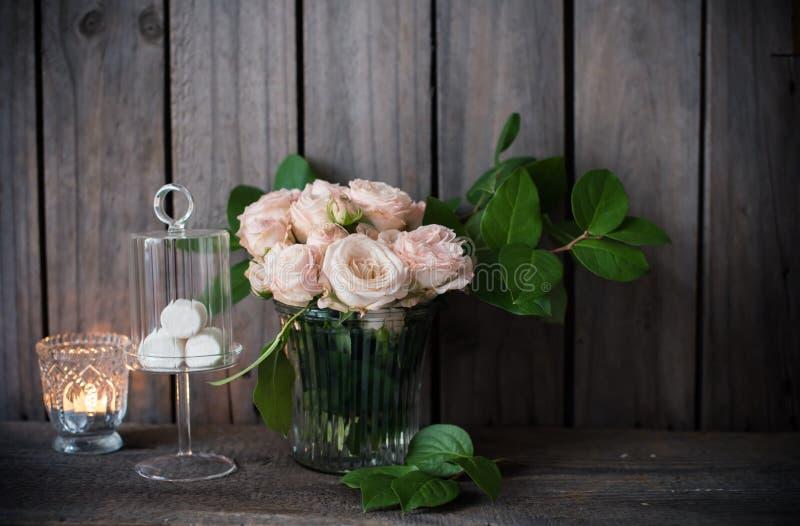 Κομψή εκλεκτής ποιότητας διακόσμηση γαμήλιων πινάκων με τα τριαντάφυλλα και τα κεριά στοκ εικόνες