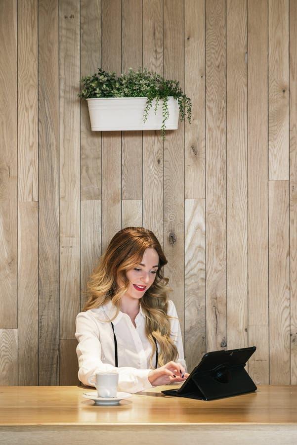 Κομψή επιχειρηματίας που εργάζεται με μια ταμπλέτα σε ένα εστιατόριο στοκ εικόνες