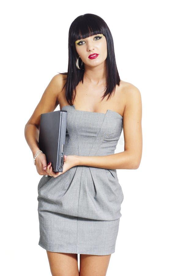 Κομψή επιχειρησιακή γυναίκα που κρατά ένα lap-top στοκ εικόνα με δικαίωμα ελεύθερης χρήσης