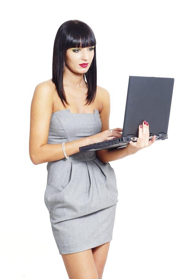 Κομψή επιχειρησιακή γυναίκα που κρατά ένα lap-top στοκ φωτογραφία