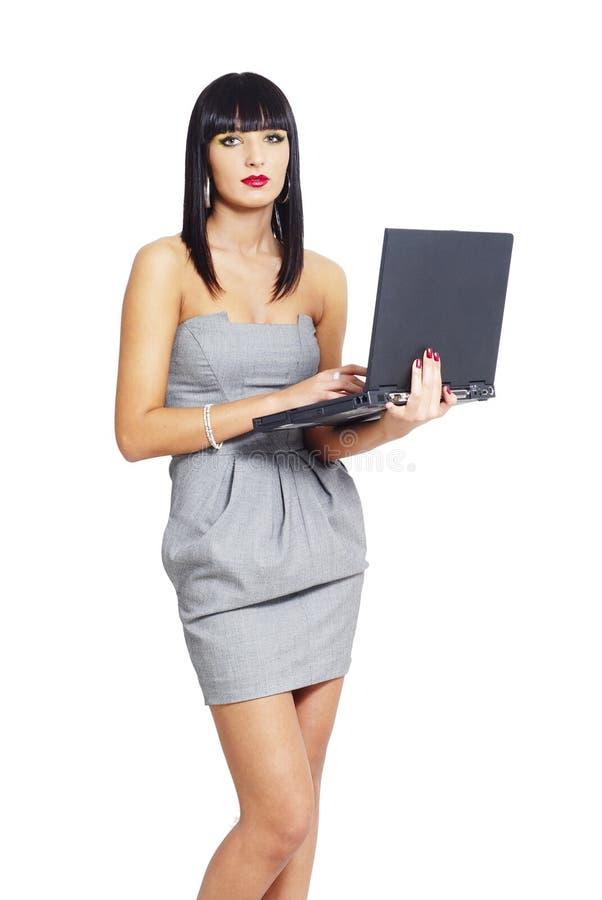 Κομψή επιχειρησιακή γυναίκα που κρατά ένα lap-top στοκ φωτογραφία με δικαίωμα ελεύθερης χρήσης
