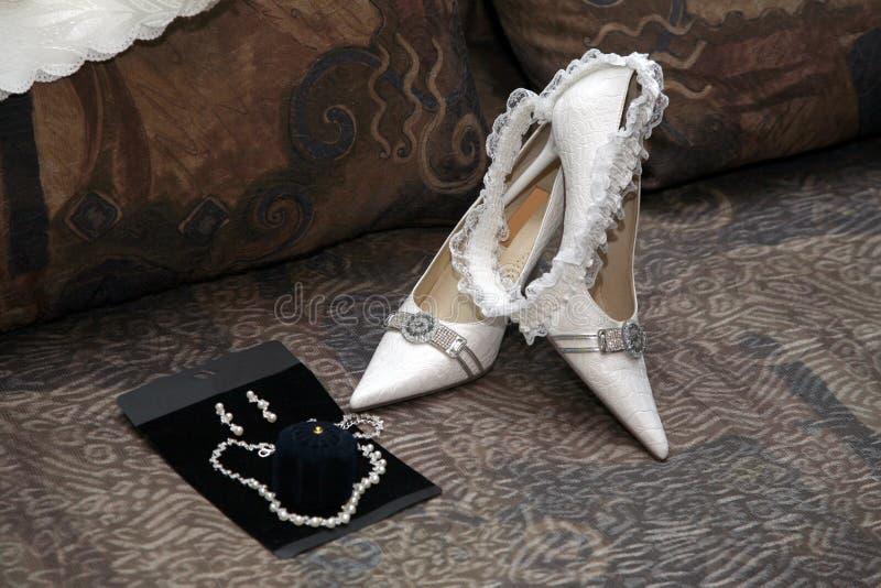 Κομψή λευκιά νύφη γαμήλιων παπουτσιών με garter στοκ εικόνα