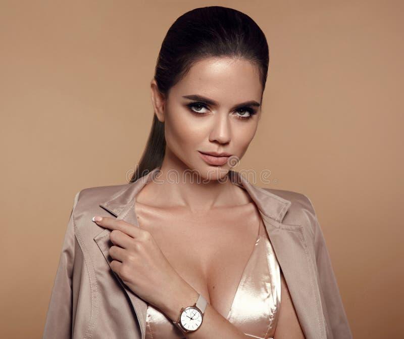 Κομψή κυρία με το wristwatch σε διαθεσιμότητα Όμορφη γυναίκα με το makeup και τη μακροχρόνια υγιή κυματιστή τοποθέτηση ύφους τρίχ στοκ εικόνα με δικαίωμα ελεύθερης χρήσης