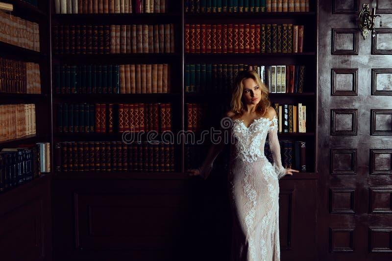 Κομψή κυρία που φορά το φόρεμα βραδιού στην παλαιά εκλεκτής ποιότητας βιβλιοθήκη Ομορφιά, μόδα στοκ φωτογραφία
