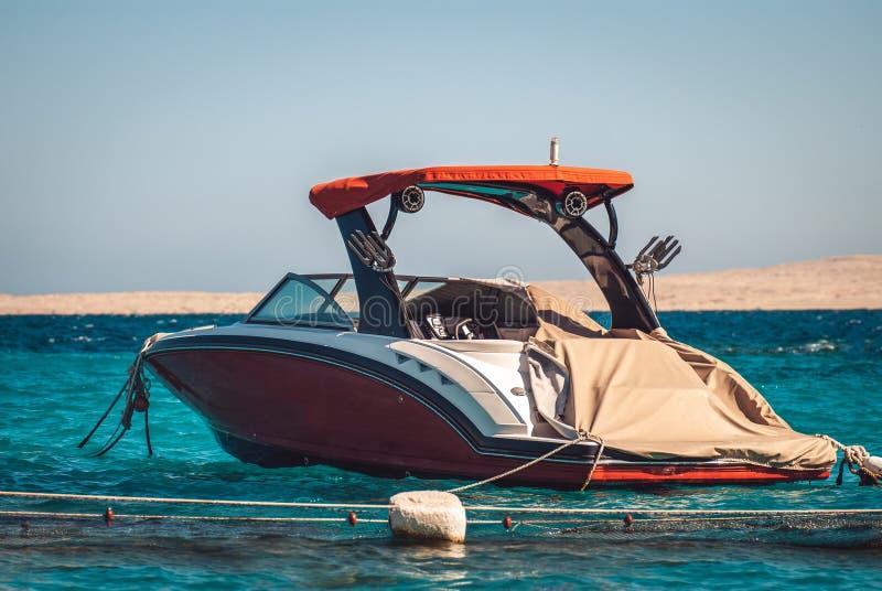 Κομψή κόκκινη βάρκα μηχανών πολυτέλειας στο υπόβαθρο της κυανής μπλε θάλασσας και μια λουρίδα των αμμωδών βουνών στο υπόβαθρο στοκ φωτογραφία με δικαίωμα ελεύθερης χρήσης