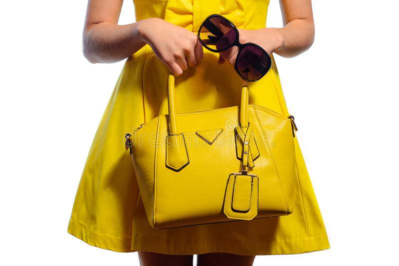 Κομψή μοντέρνη γυναίκα στο κίτρινο φόρεμα με την τσάντα και τα γυαλιά ηλίου στοκ φωτογραφίες