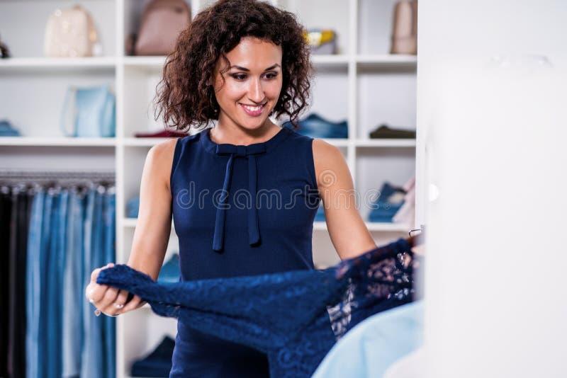 Κομψή νέα γυναίκα που ψάχνει ένα νέο φόρεμα στο κατάστημα ιματισμού στοκ φωτογραφίες με δικαίωμα ελεύθερης χρήσης