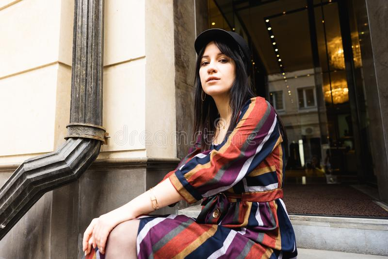 Κομψή νέα γυναίκα σε ένα πολύχρωμα ριγωτά φόρεμα και ένα μαύρο καπέλο στοκ εικόνες με δικαίωμα ελεύθερης χρήσης