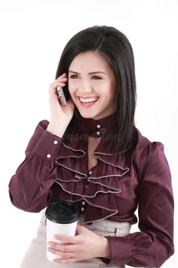 Κομψή νέα γυναίκα Brunette με τον καφέ που μιλά από το τηλεφωνικό isol στοκ εικόνες