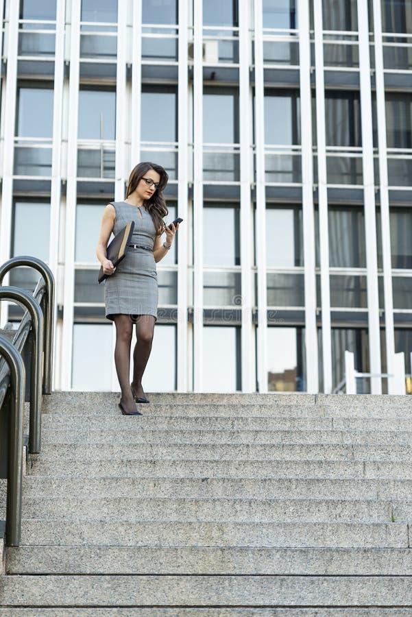 Κομψή νέα επιχειρηματίας που γράφει το ηλεκτρονικό ταχυδρομείο τηλεφωνικώς στοκ εικόνες