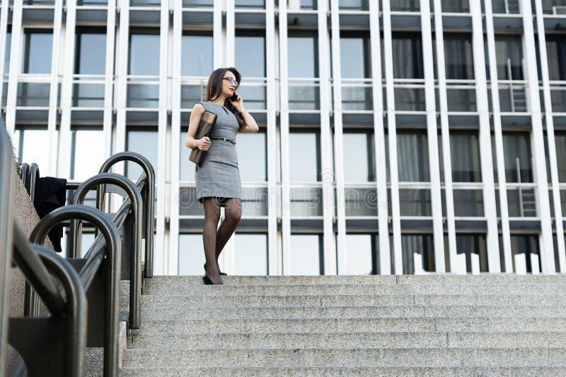 Κομψή νέα επιχειρηματίας που μιλά τηλεφωνικώς στοκ φωτογραφία