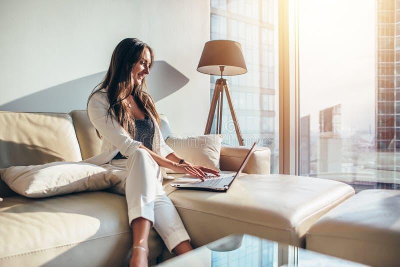 Κομψή νέα θηλυκή επιχειρησιακή γυναίκα που χρησιμοποιεί μια συνεδρίαση lap-top σε έναν καναπέ στο σπίτι στοκ φωτογραφία με δικαίωμα ελεύθερης χρήσης