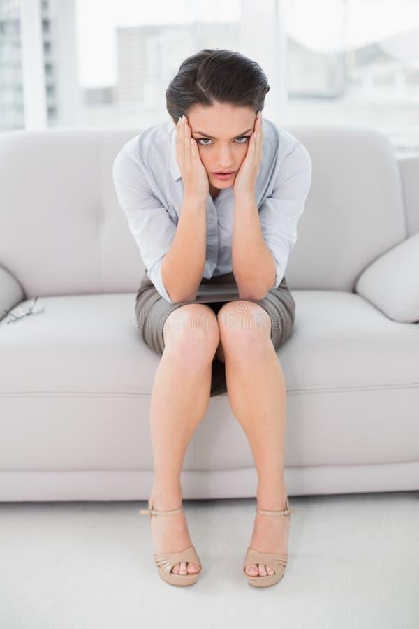 Κομψή νέα συνεδρίαση γυναικών με το κεφάλι στα χέρια στον καναπέ στοκ εικόνες με δικαίωμα ελεύθερης χρήσης