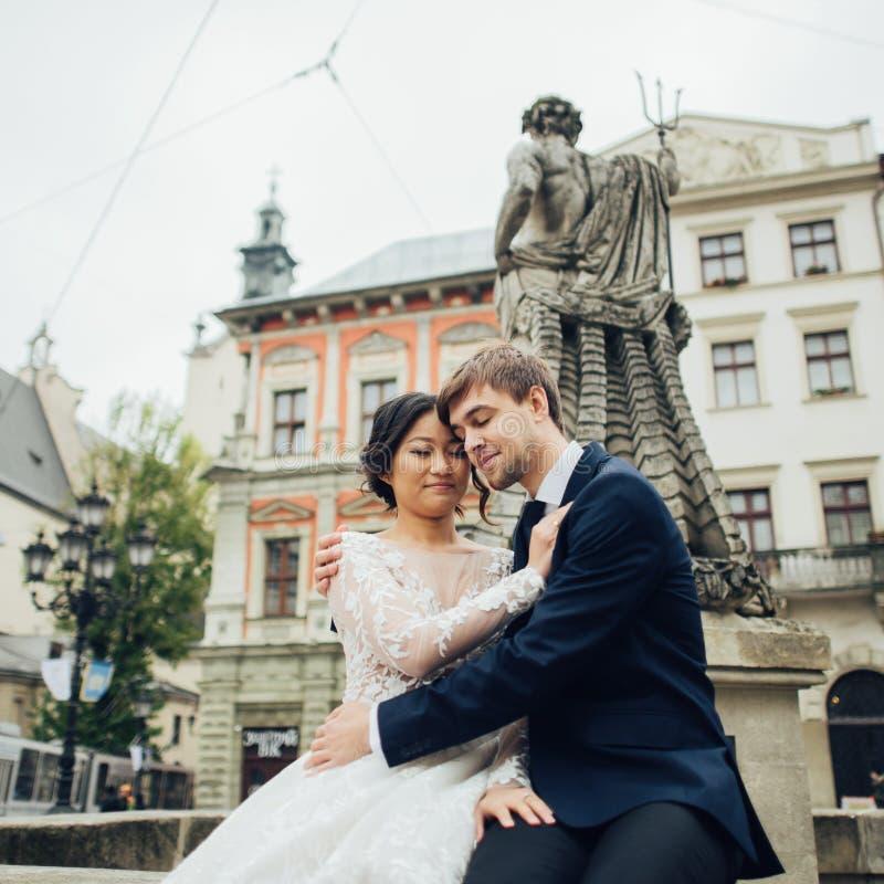 Κομψή νύφη με το νεόνυμφο που περπατά κοντά στον παλαιό καθολικό καθεδρικό ναό στοκ εικόνα με δικαίωμα ελεύθερης χρήσης