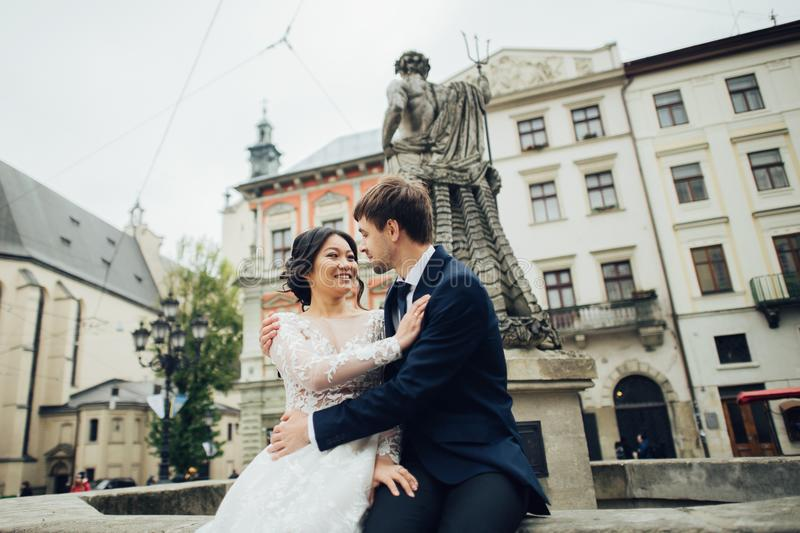 Κομψή νύφη με το νεόνυμφο που περπατά κοντά στον παλαιό καθολικό καθεδρικό ναό στοκ εικόνες