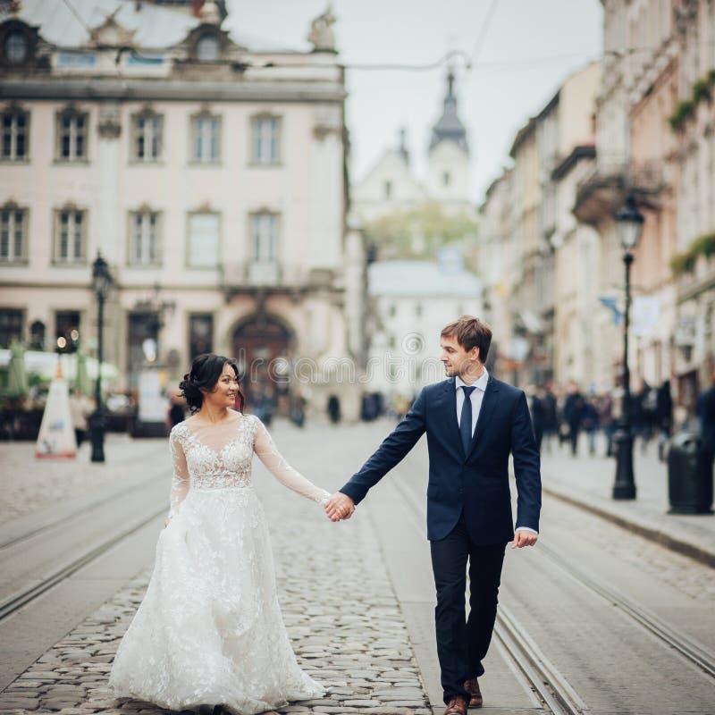 Κομψή νύφη με το νεόνυμφο που περπατά κοντά στον παλαιό καθολικό καθεδρικό ναό στοκ φωτογραφία