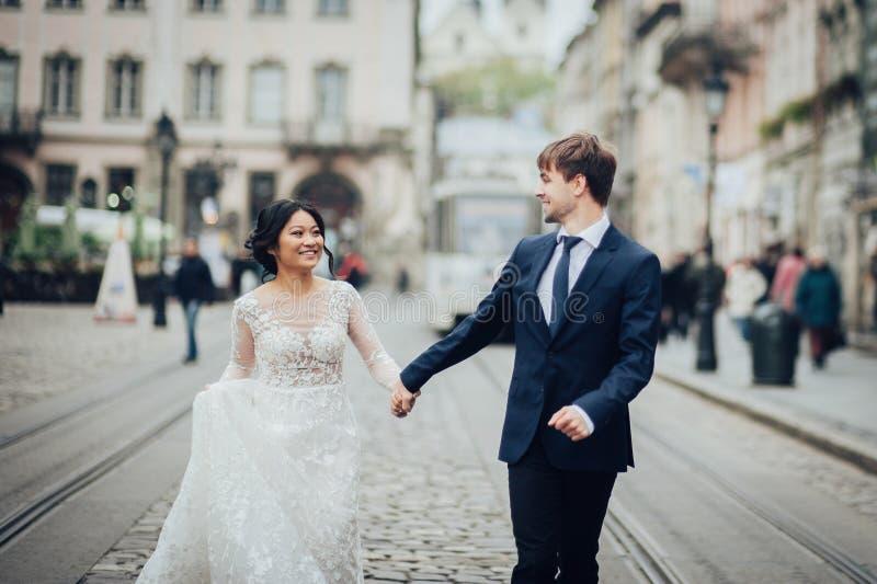 Κομψή νύφη με το νεόνυμφο που περπατά κοντά στον παλαιό καθολικό καθεδρικό ναό στοκ εικόνες με δικαίωμα ελεύθερης χρήσης