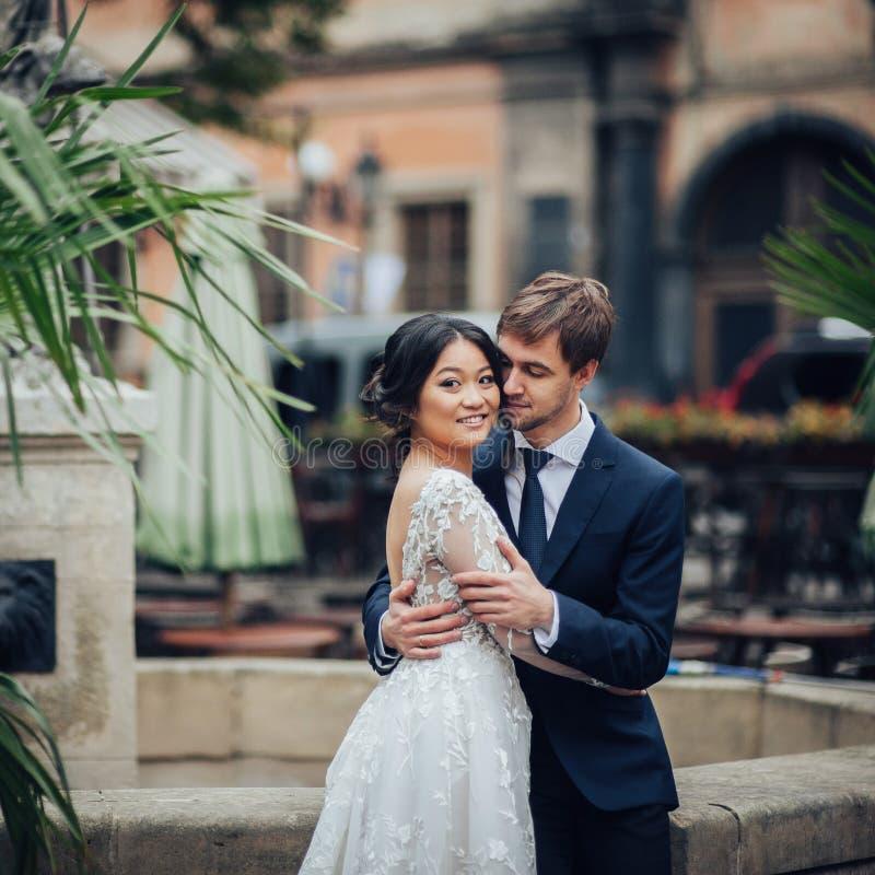 Κομψή νύφη με το νεόνυμφο που περπατά κοντά στον παλαιό καθολικό καθεδρικό ναό στοκ φωτογραφία με δικαίωμα ελεύθερης χρήσης