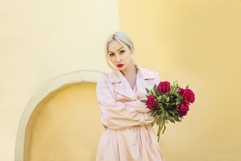 Κομψή ξανθή γυναίκα με τα peony λουλούδια υπαίθρια στοκ φωτογραφία με δικαίωμα ελεύθερης χρήσης