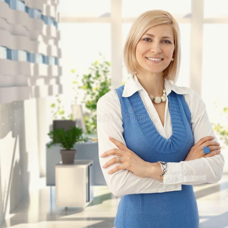 Κομψή ξανθή γυναίκα που χαμογελά στο γραφείο στοκ εικόνες με δικαίωμα ελεύθερης χρήσης