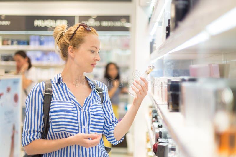 Κομψή ξανθή νέα γυναίκα που επιλέγει το άρωμα στο μαγαζί λιανικής πώλησης στοκ εικόνες