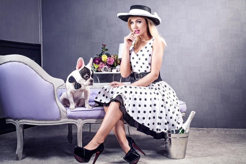 Κομψή ξανθή τοποθέτηση γυναικών με το σκυλί μαλαγμένου πηλού στοκ φωτογραφία με δικαίωμα ελεύθερης χρήσης