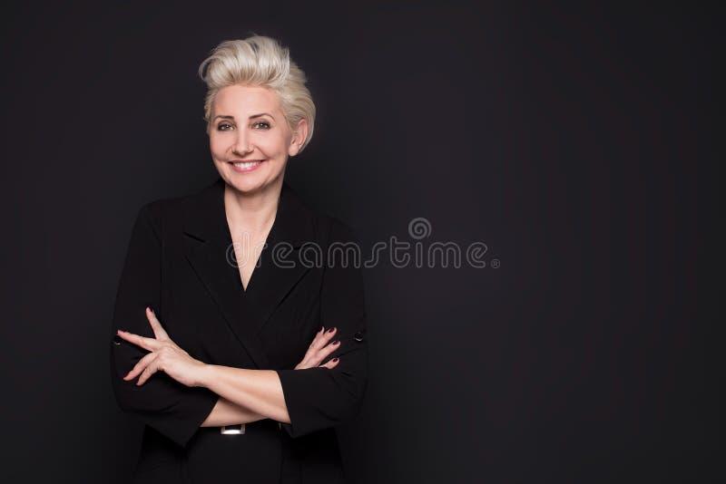Κομψή ξανθή όμορφη μέση ηλικίας γυναικεία τοποθέτηση στοκ φωτογραφίες