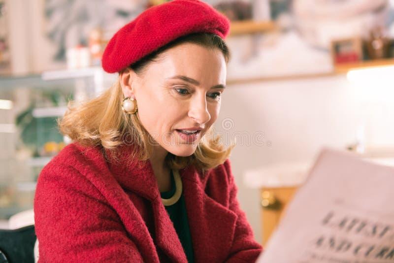 Κομψή ώριμη γαλλική γυναίκα που φορά beret την εφημερίδα ανάγνωσης στοκ εικόνες με δικαίωμα ελεύθερης χρήσης