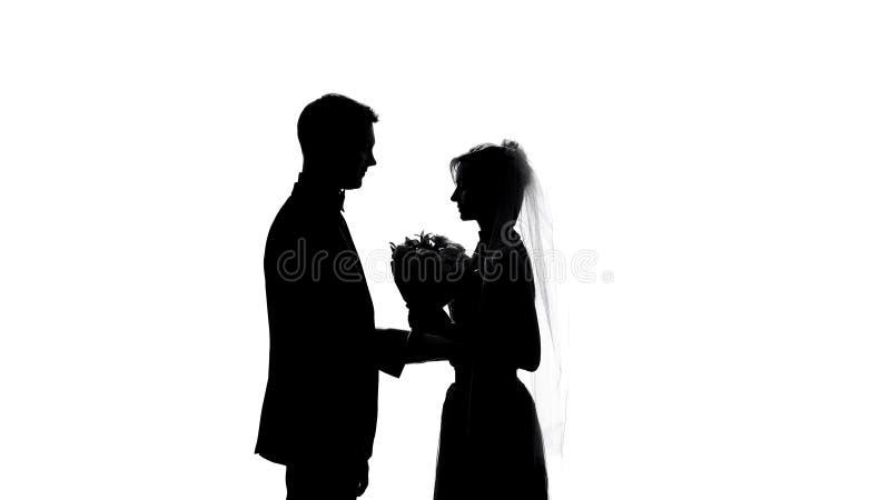 Κομψοί νεόνυμφος και νύφη με την ανθοδέσμη, σκιαγραφίες γαμήλιας τελετής, γάμος στοκ φωτογραφία