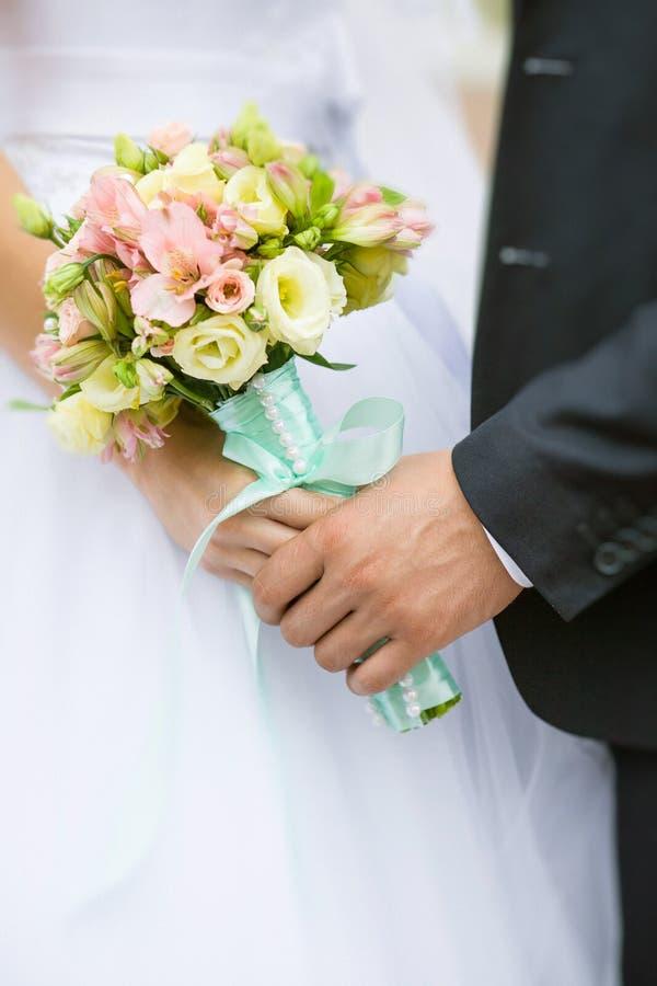 Κομψοί νύφη και νεόνυμφος που κρατά την όμορφη γαμήλια ανθοδέσμη θέτοΠστοκ φωτογραφία με δικαίωμα ελεύθερης χρήσης