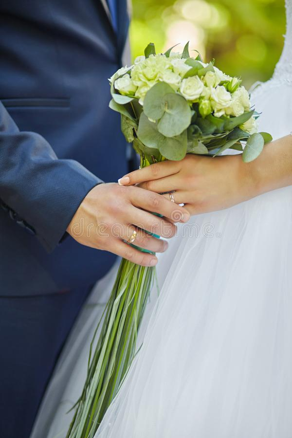 Κομψοί νύφη και νεόνυμφος που κρατά την όμορφη γαμήλια ανθοδέσμη θέτοΠστοκ φωτογραφία
