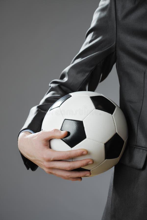 Κομψός επιχειρηματίας που κρατά μια σφαίρα ποδοσφαίρου στοκ εικόνα