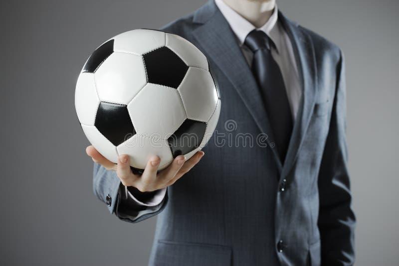 Κομψός επιχειρηματίας που κρατά μια σφαίρα ποδοσφαίρου στοκ φωτογραφία