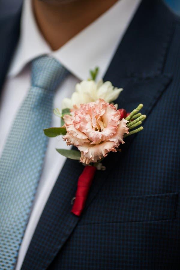 Κομψός μοντέρνος νεόνυμφος στο μαύρο κοστούμι με το φρέσκο λουλούδι πιό boutonnier στοκ εικόνες