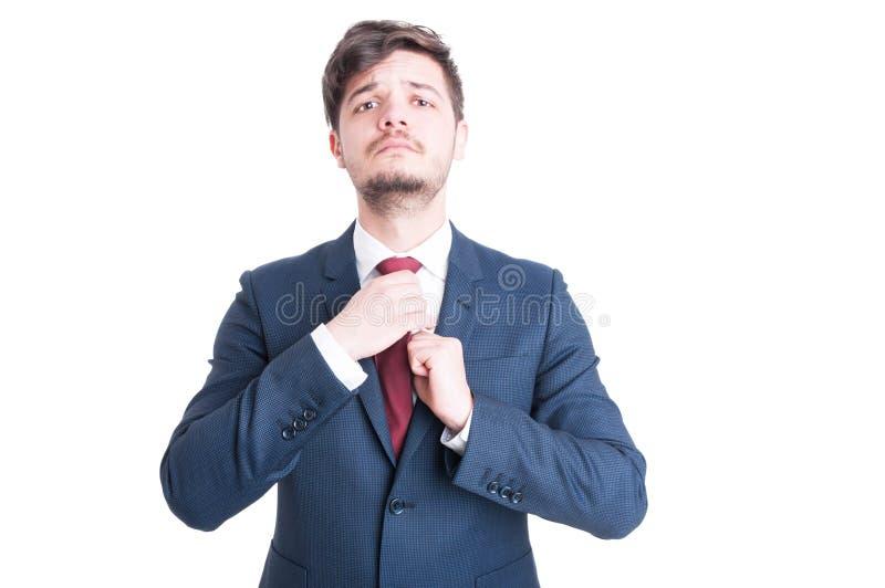 Κομψός νεαρός άνδρας που τακτοποιεί το δεσμό που φορά το κομψό κοστούμι στοκ εικόνες με δικαίωμα ελεύθερης χρήσης