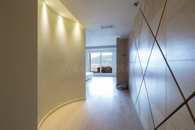 Κομψός ξύλινος διάδρομος με τα επίκεντρα στο σύγχρονο διαμέρισμα στοκ εικόνα με δικαίωμα ελεύθερης χρήσης