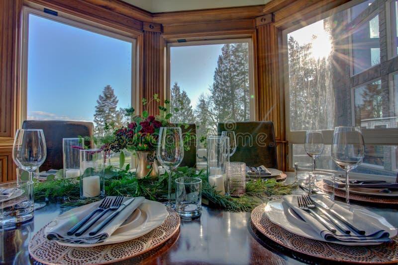 Κομψός πίνακας που τίθεται για το γεύμα και την όμορφη άποψη παραθύρων στοκ φωτογραφία