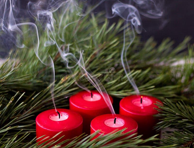 Κομψός πράσινος κλάδος και κόκκινα εκλείψας κεριά εμφάνισης από τους οποίους ο καπνός προέρχεται στοκ φωτογραφία