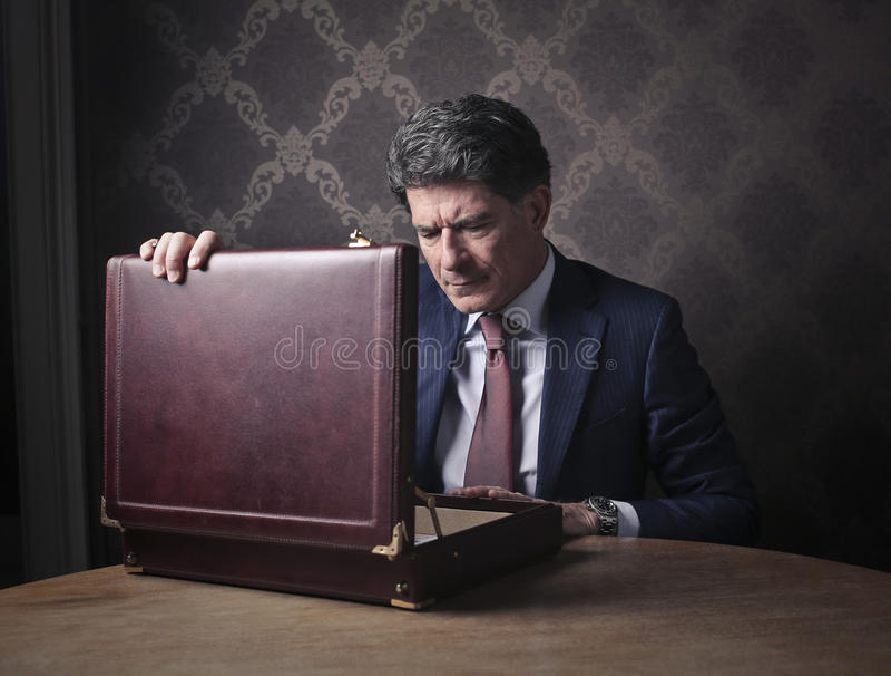 Κομψός πλούσιος άνθρωπος που ανοίγει το χαρτοφύλακά του στοκ εικόνες