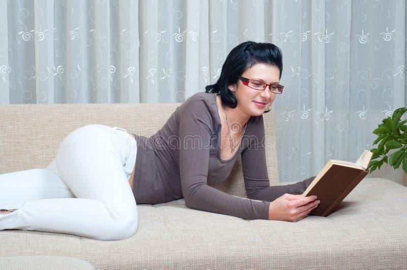 κομψός όμορφος καναπέδων βιβλίων διαβάζει τη γυναίκα στοκ φωτογραφία
