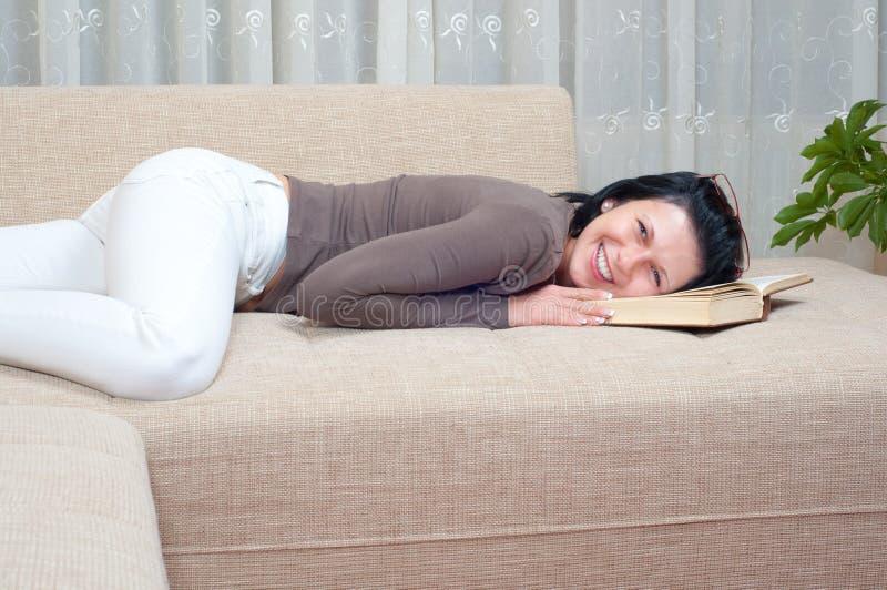 κομψός όμορφος καναπέδων βιβλίων διαβάζει τη γυναίκα στοκ εικόνες