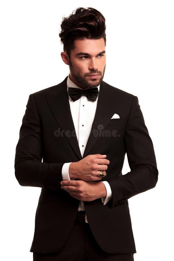 Κομψό άτομο μόδας στο σμόκιν που καθορίζει το μανίκι του στοκ φωτογραφία με δικαίωμα ελεύθερης χρήσης