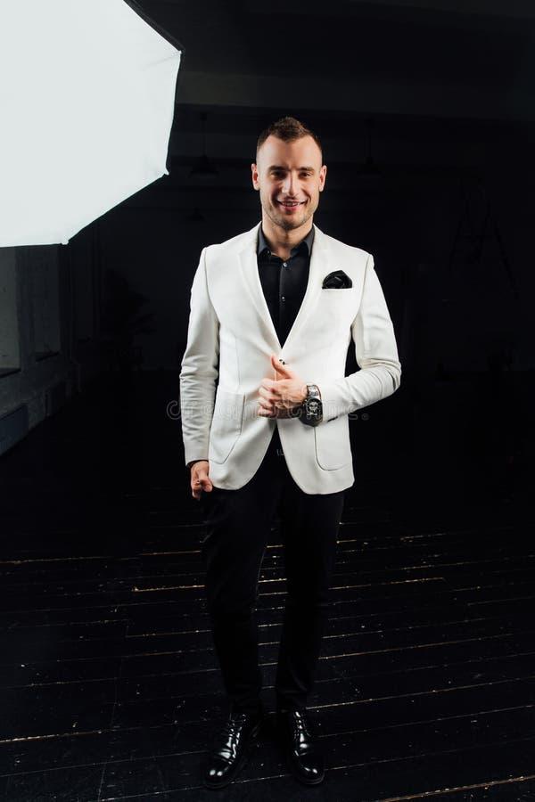 Κομψό άτομο σε ένα άσπρο κοστούμι με τις σκληρές τρίχες και ένα χαρτομάνδηλο στούντιο ptrait σε ένα σκοτεινό υπόβαθρο στοκ εικόνα με δικαίωμα ελεύθερης χρήσης