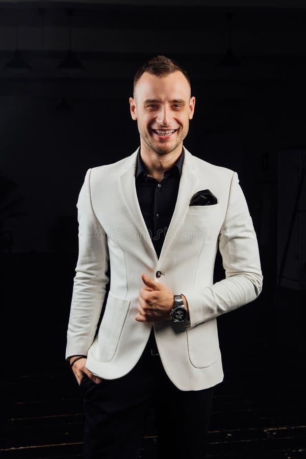 Κομψό άτομο σε ένα άσπρο κοστούμι με τις σκληρές τρίχες και ένα χαρτομάνδηλο στούντιο ptrait σε ένα σκοτεινό υπόβαθρο στοκ εικόνες