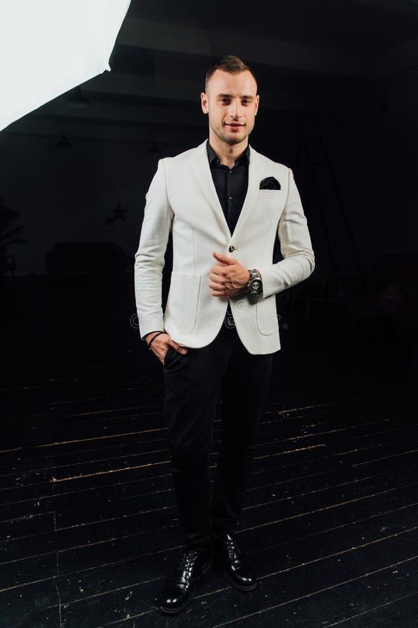 Κομψό άτομο σε ένα άσπρο κοστούμι με τις σκληρές τρίχες και ένα χαρτομάνδηλο στούντιο ptrait σε ένα σκοτεινό υπόβαθρο στοκ εικόνα