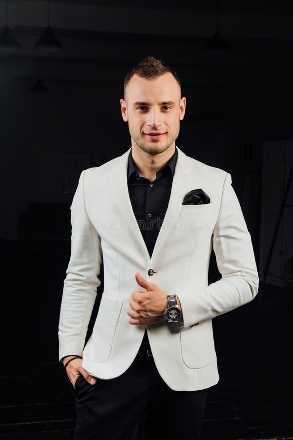 Κομψό άτομο σε ένα άσπρο κοστούμι με τις σκληρές τρίχες και ένα χαρτομάνδηλο στούντιο ptrait σε ένα σκοτεινό υπόβαθρο στοκ φωτογραφία με δικαίωμα ελεύθερης χρήσης