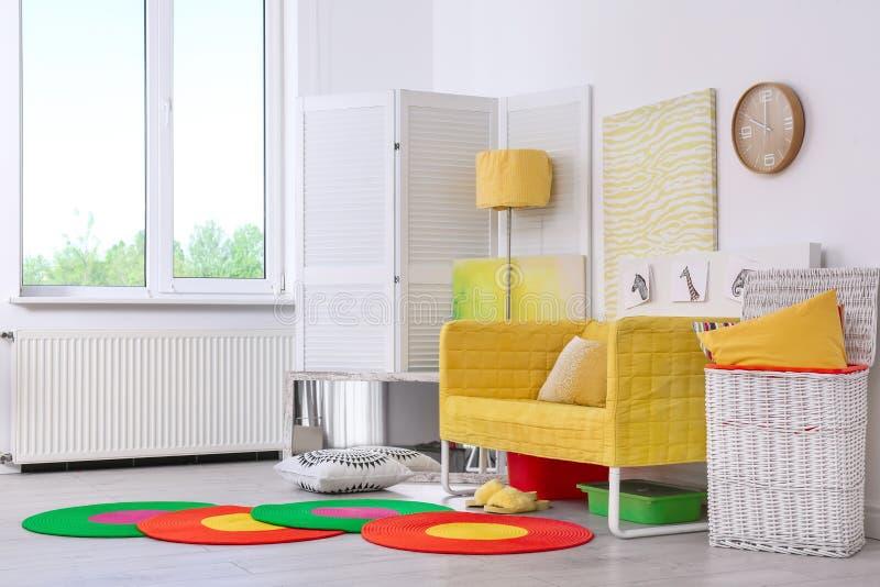 Κομψό εσωτερικό καθιστικών με τον άνετο καναπέ Ιδέα για το εγχώριο σχέδιο στα χρώματα ουράνιων τόξων στοκ εικόνες με δικαίωμα ελεύθερης χρήσης