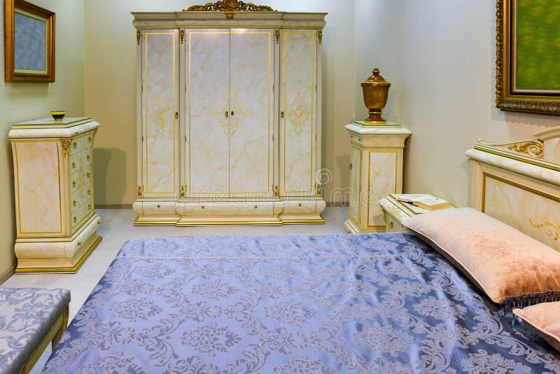 Κομψό εσωτερικό κρεβατοκάμαρων με το μεγάλο κρεβάτι στοκ φωτογραφίες με δικαίωμα ελεύθερης χρήσης