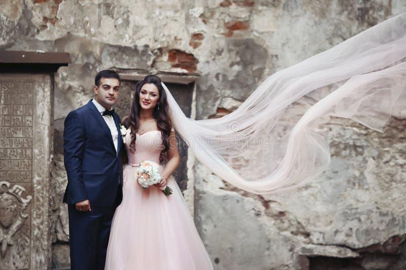 Κομψό ζεύγος των newlyweds που θέτουν μπροστά από τον παλαιό τοίχο W εκκλησιών στοκ φωτογραφία με δικαίωμα ελεύθερης χρήσης
