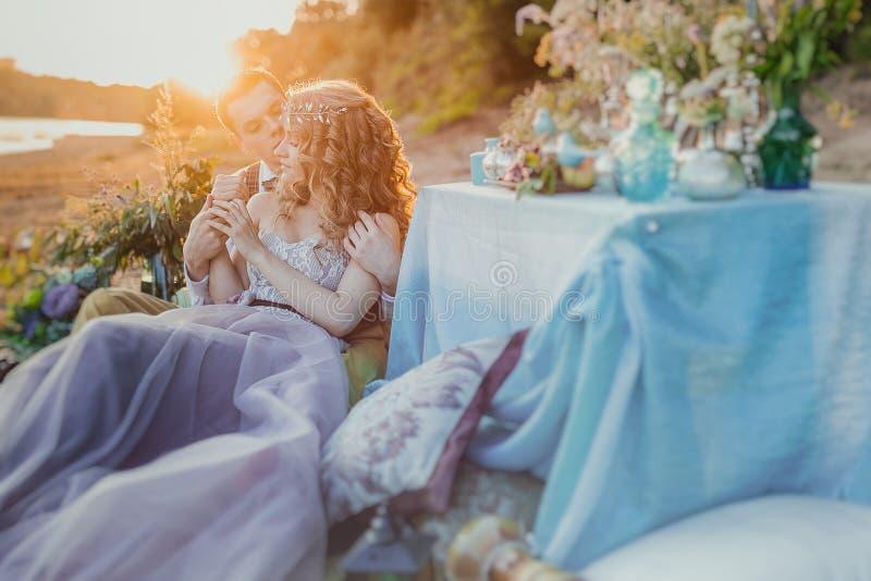 Κομψό ζεύγος Boho ερωτευμένο η νύφη και ο νεόνυμφος Πικ-νίκ γαμήλιας έμπνευσης υπαίθρια, με τον πίνακα γευμάτων και το ντεκόρ τυρ στοκ εικόνες